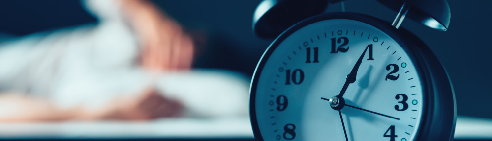 Sleeping disorder or insomnia concept, selective focus of vintage clock in bedroom and out of focus male person trying to fall asleep in bed